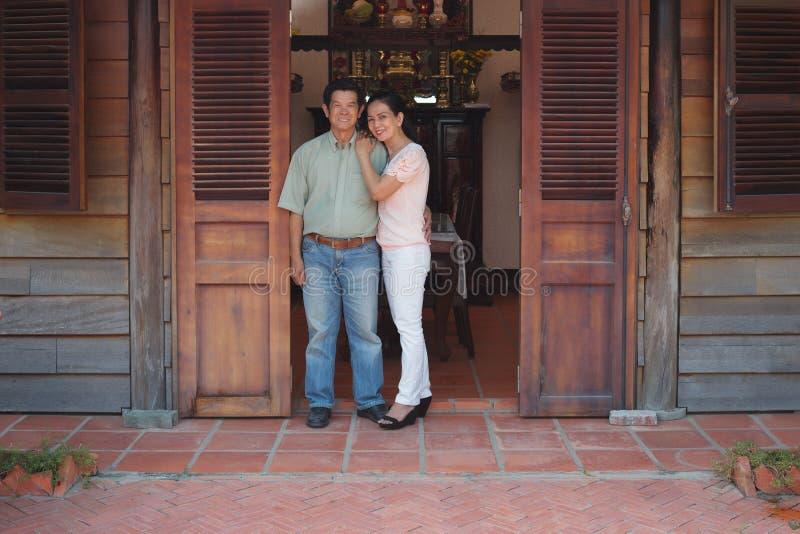 Pares asiáticos na frente de sua casa fotos de stock royalty free