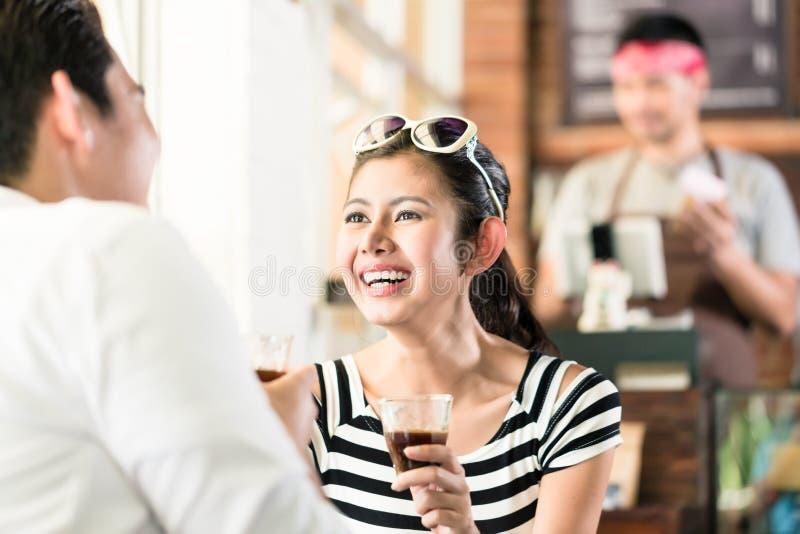 Pares asiáticos no café que flerta ao beber o café fotografia de stock