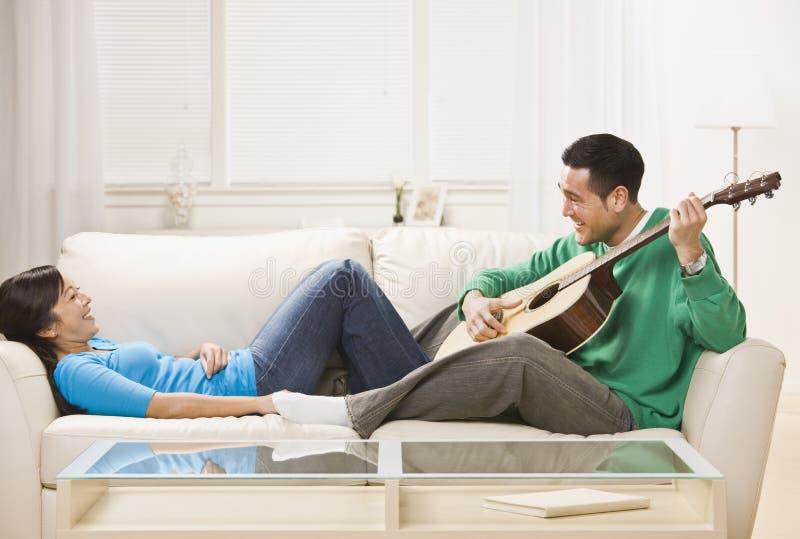 Pares asiáticos no sofá que relaxa junto. foto de stock royalty free