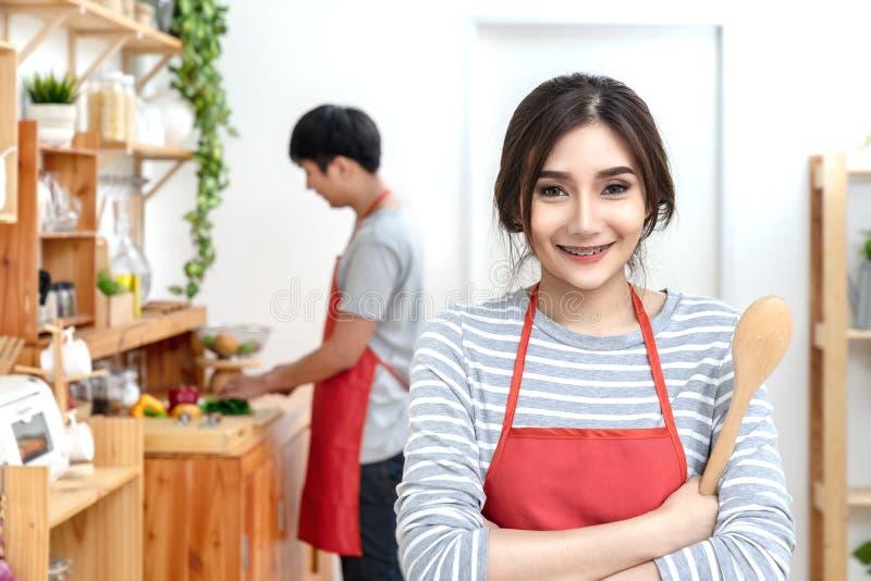 Pares asiáticos novos atrativos que vestem o avental alaranjado ocasional que cozinha a refeição na cozinha de madeira em casa ou foto de stock royalty free
