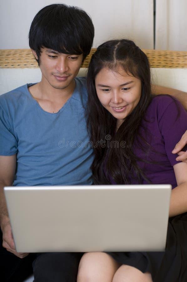 Pares asiáticos novos com computador imagens de stock royalty free