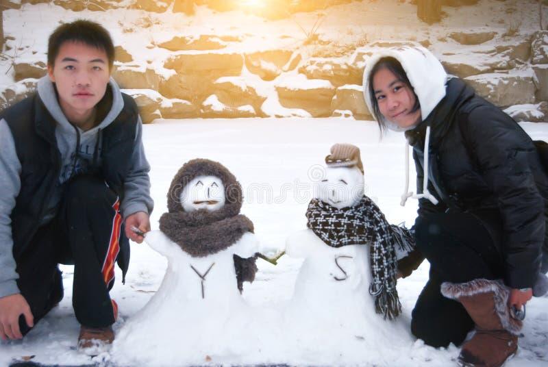 Pares asiáticos novos com Snowmans imagem de stock royalty free