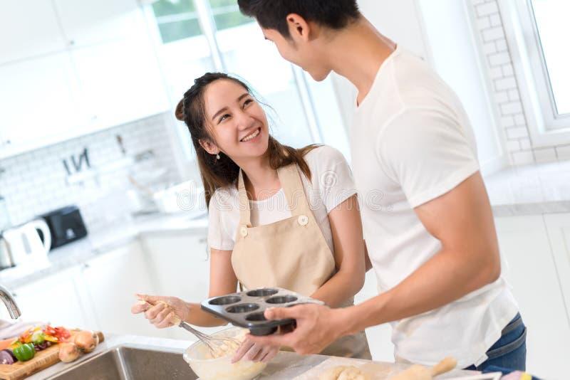 Pares asiáticos novos do homem e da mulher que fazem junto a padaria endurecer e panar fotografia de stock