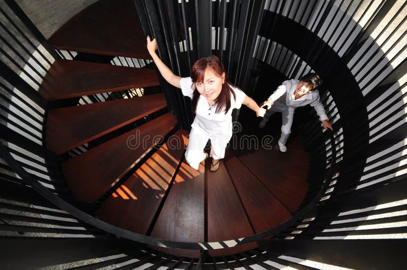 Pares asiáticos novos em escadas de escalada do amor imagens de stock
