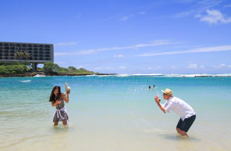Pares asiáticos novos felizes que jogam com água na praia de Havaí foto de stock