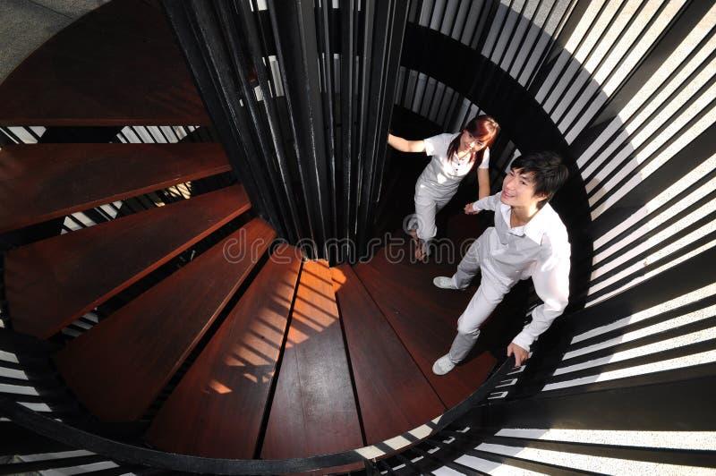 Pares asiáticos novos no amor que escala escadas espirais fotos de stock