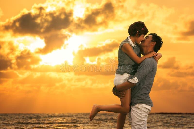 Pares asiáticos novos no amor que fica e que beija na praia foto de stock royalty free