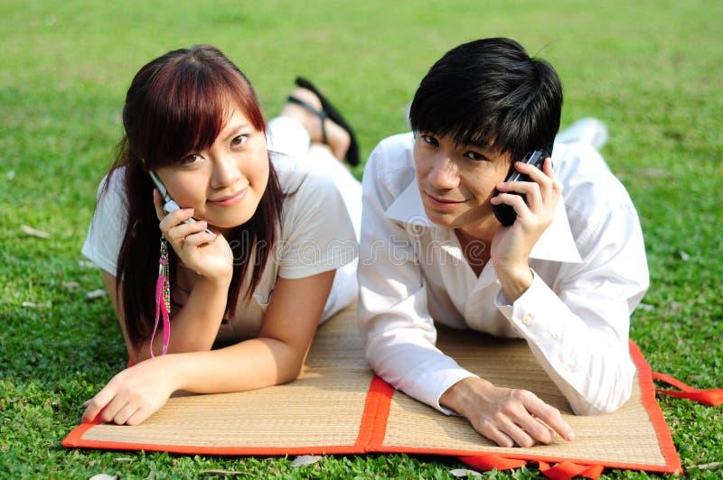 Pares asiáticos novos no amor usando o móbil fotografia de stock royalty free