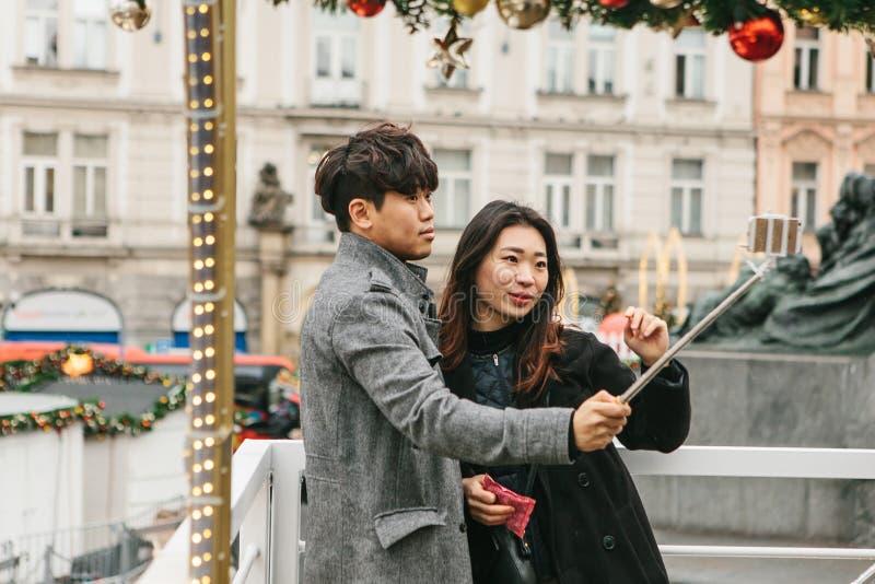 Pares asiáticos novos que tomam o selfie na memória de Praga em República Checa durante os feriados do Natal imagem de stock