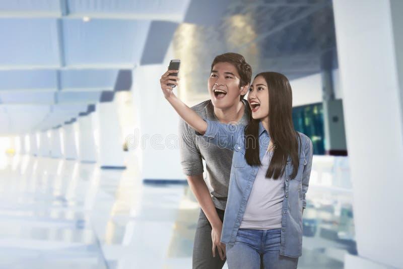 Pares asiáticos novos que tomam o selfie pelo smartphone foto de stock