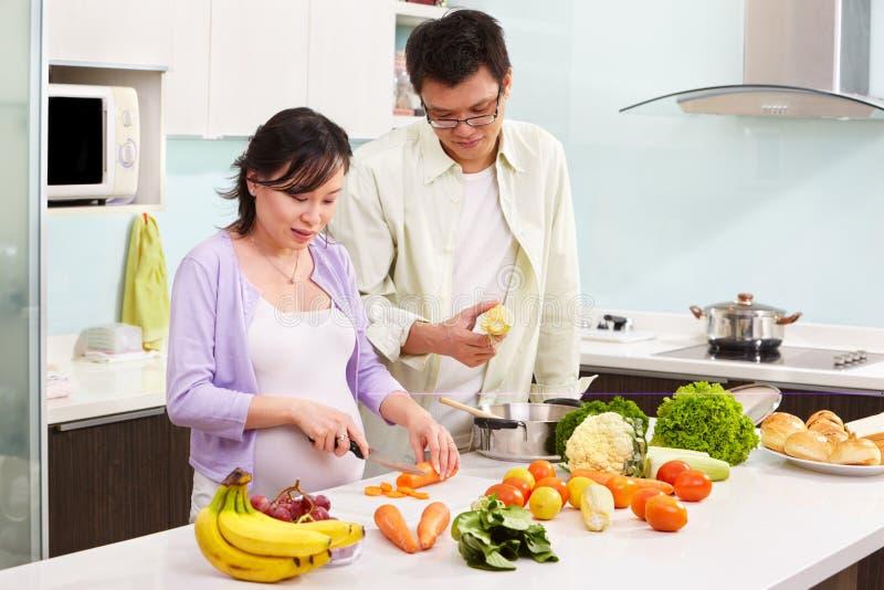 Pares asiáticos ocupados na cozinha imagem de stock