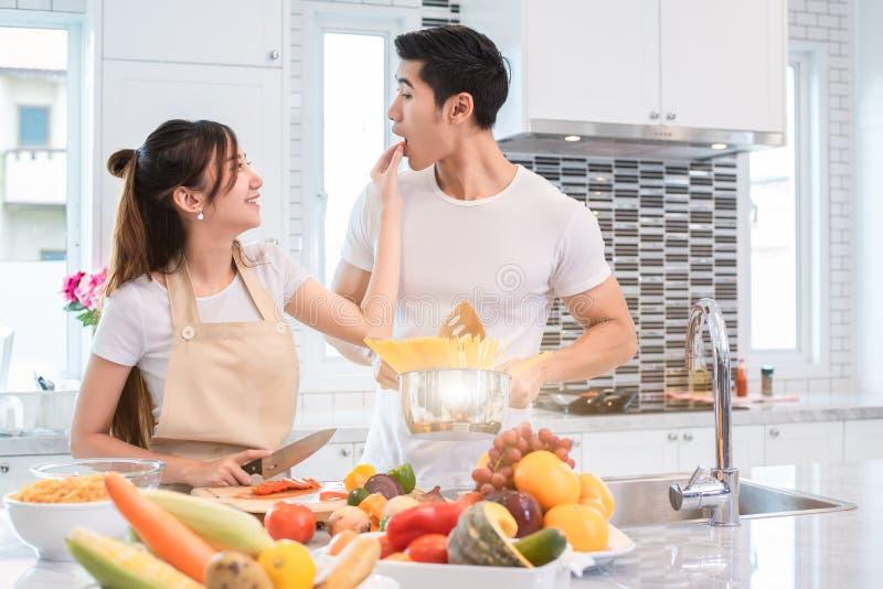 Pares asiáticos que alimentam o alimento junto na cozinha Povos e lifes fotografia de stock royalty free