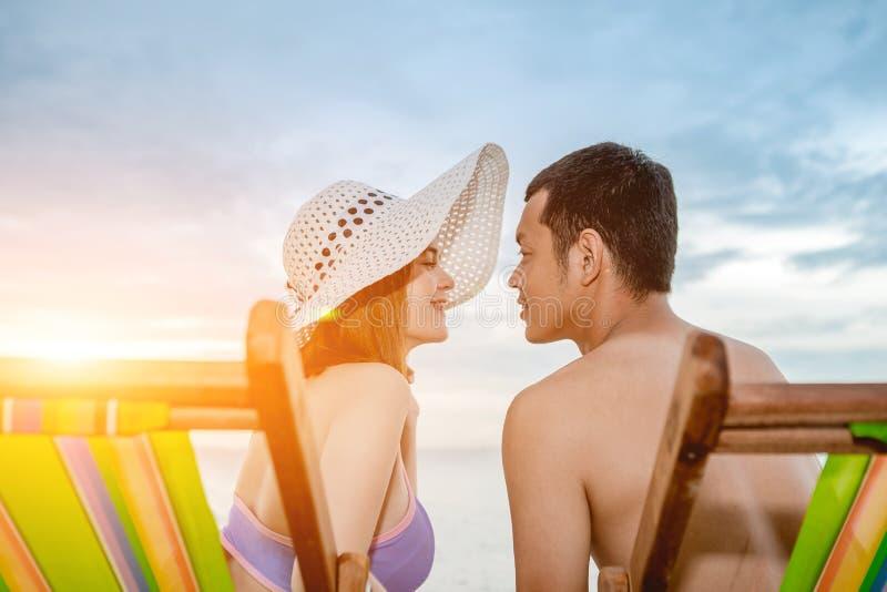 Pares asiáticos que caminan en la playa cuando el sol está alrededor a la puesta del sol durante la luna de miel imagen de archivo libre de regalías