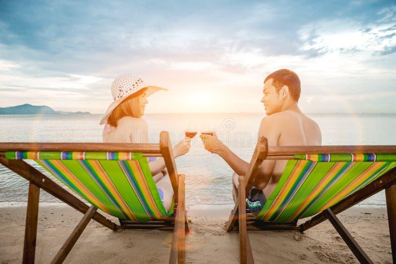 Pares asiáticos que caminan en la playa cuando el sol está alrededor a la puesta del sol durante la luna de miel imagenes de archivo
