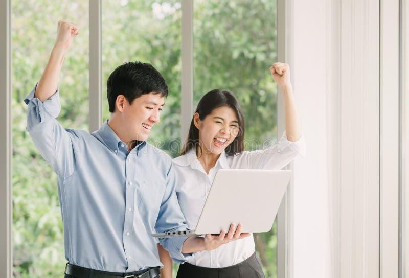 Pares asiáticos que celebran éxito con el ordenador portátil imagen de archivo