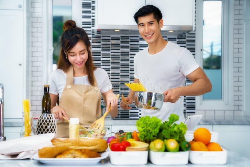 Pares asiáticos que cocinan para la comida y la ensalada fotos de archivo libres de regalías