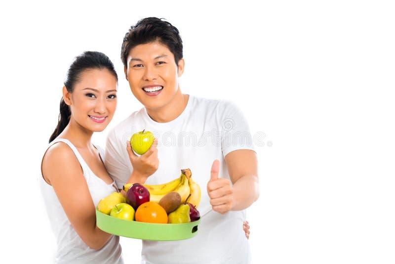 Pares asiáticos que comem frutos saudáveis foto de stock royalty free