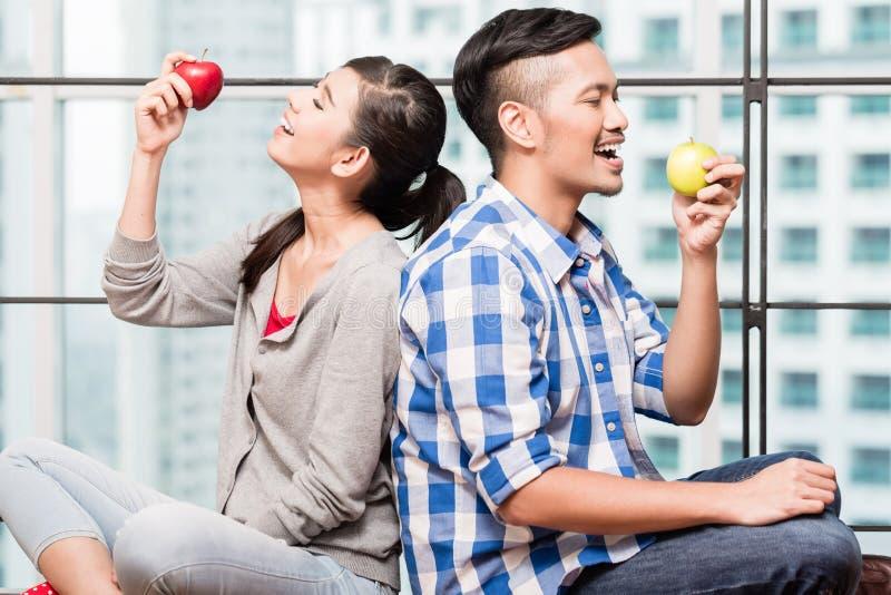 Pares asiáticos que comen manzanas como bocado sano imagen de archivo