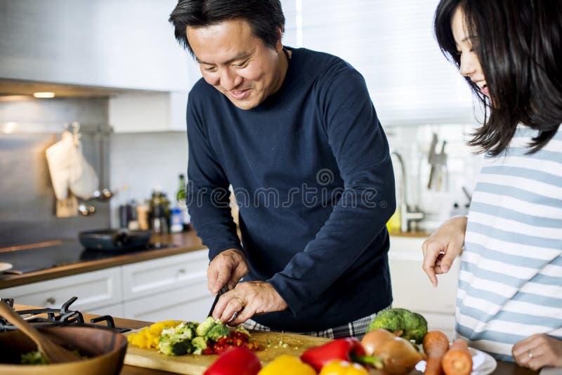 Pares asiáticos que cozinham na cozinha imagem de stock