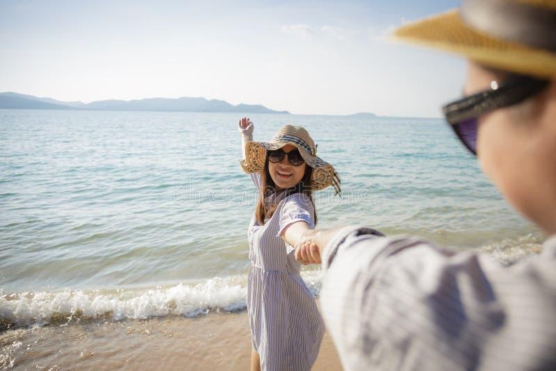 Pares asi?ticos que disfrutan de vacaciones de la playa en la playa, novia sonriente que camina con la mano de la tenencia de su  fotografía de archivo
