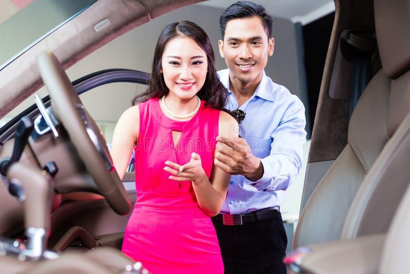Pares asiáticos que eligen el coche de lujo en la representación imagen de archivo libre de regalías