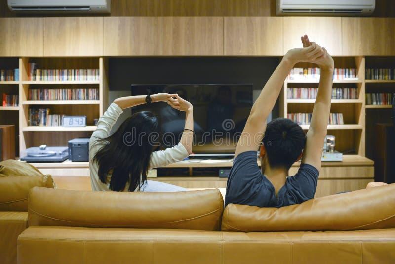 Pares asiáticos que esticam para fora seus braços na frente da tevê na noite fotografia de stock