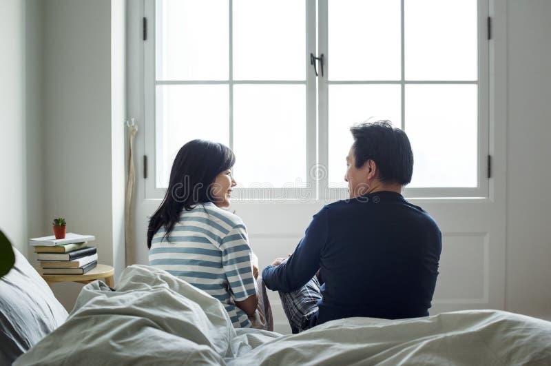 Pares asiáticos que hablan junto en cama fotos de archivo