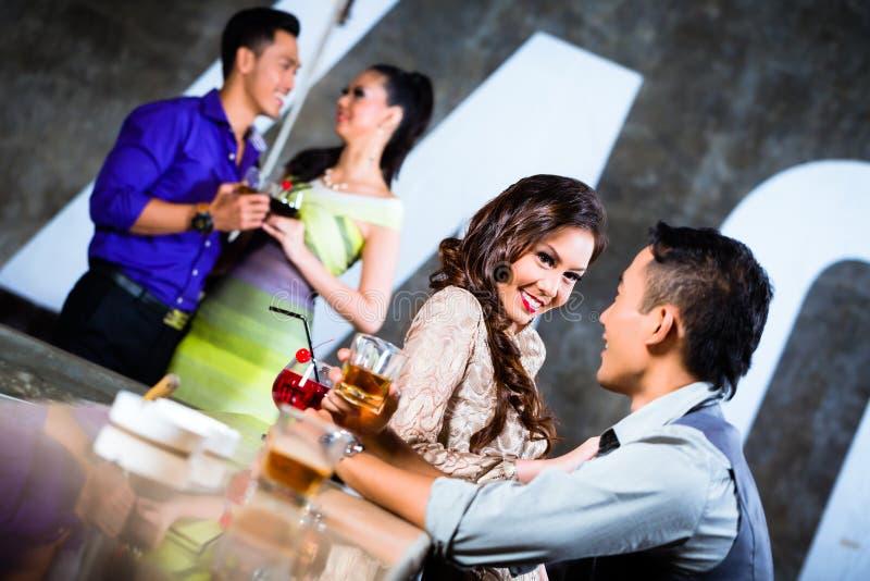 Pares asiáticos que ligan y que beben en la barra del club nocturno fotografía de archivo