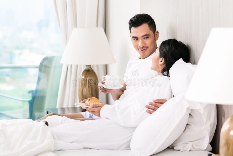 Pares asiáticos que lounging na cama imagens de stock
