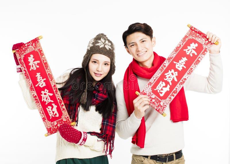 pares asiáticos que mostram dísticos vermelhos anos novos chineses felizes imagens de stock royalty free