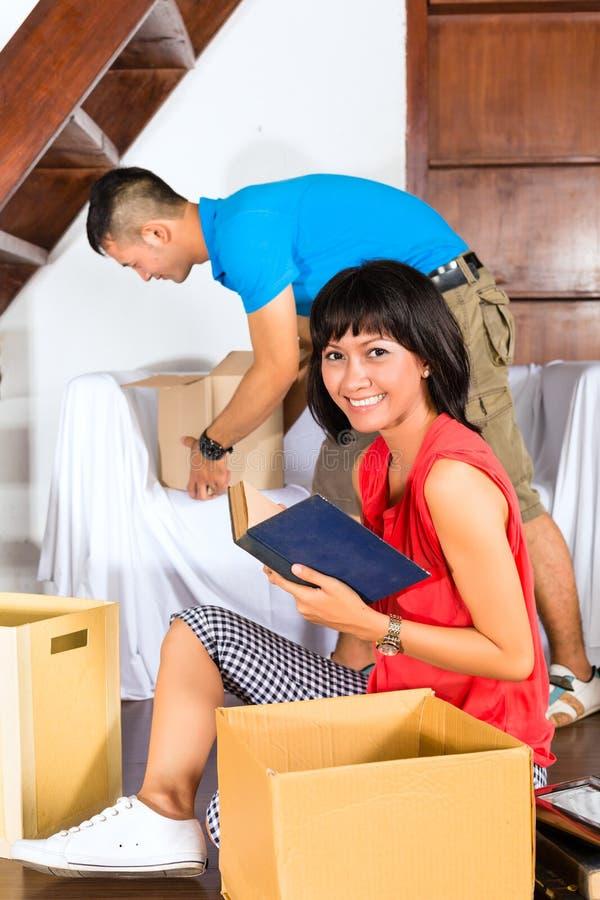 Pares asiáticos que movem-se na casa nova fotos de stock