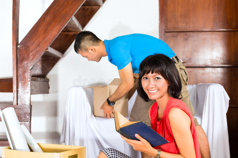 Pares asiáticos que movem-se na casa nova imagens de stock