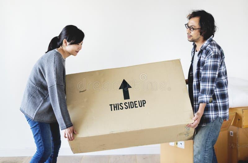 Pares asiáticos que movem-se para a casa nova imagem de stock