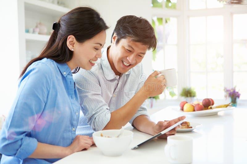 Pares asiáticos que olham a tabuleta de Digitas sobre o café da manhã imagens de stock royalty free