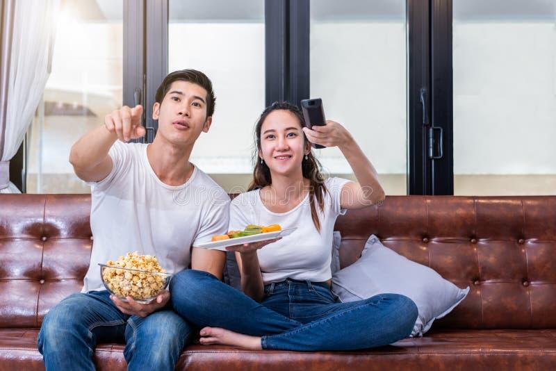 Pares asiáticos que olham a televisão junto no sofá em sua casa imagens de stock royalty free
