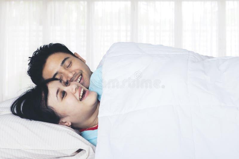 Pares asiáticos que riem junto na cama foto de stock