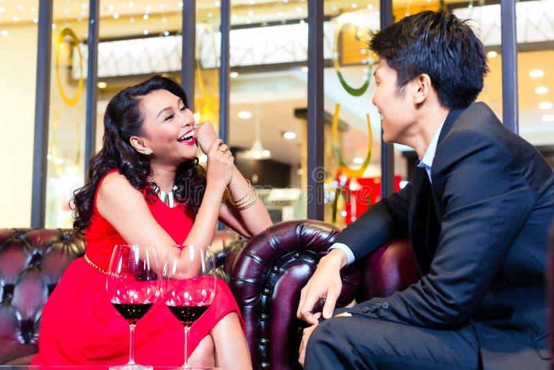 Pares asiáticos que sentam-se na conversa da barra fotografia de stock royalty free