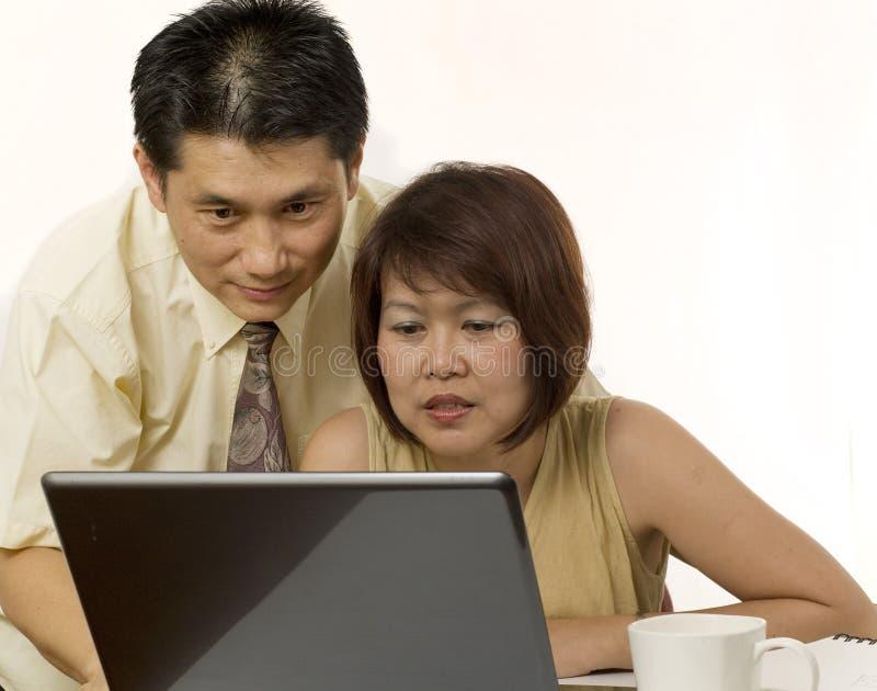 Pares asiáticos que surfam o Internet fotografia de stock
