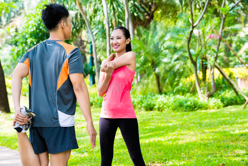 Pares asiáticos que têm o treinamento exterior do esporte da aptidão imagens de stock