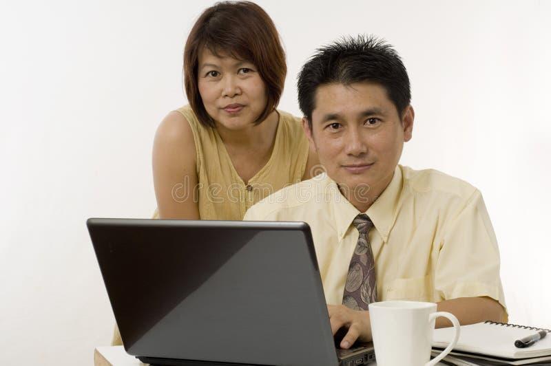 Pares asiáticos que trabalham junto foto de stock