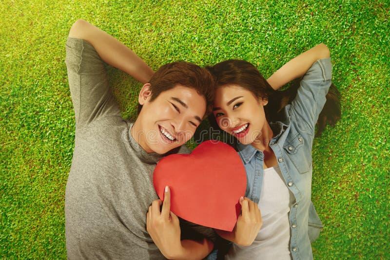 Pares asiáticos românticos que guardam a forma do coração imagem de stock