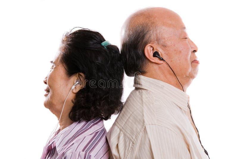 Pares asiáticos sênior que escutam a música imagens de stock
