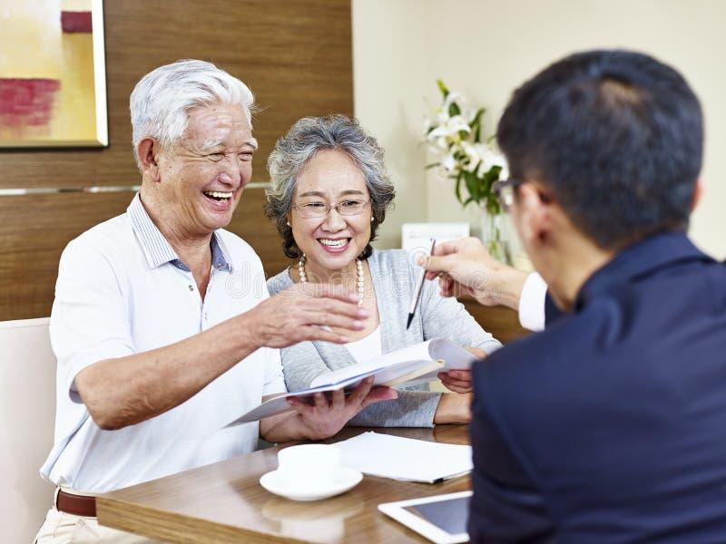 Pares asiáticos superiores prontos para assinar o contrato fotografia de stock royalty free