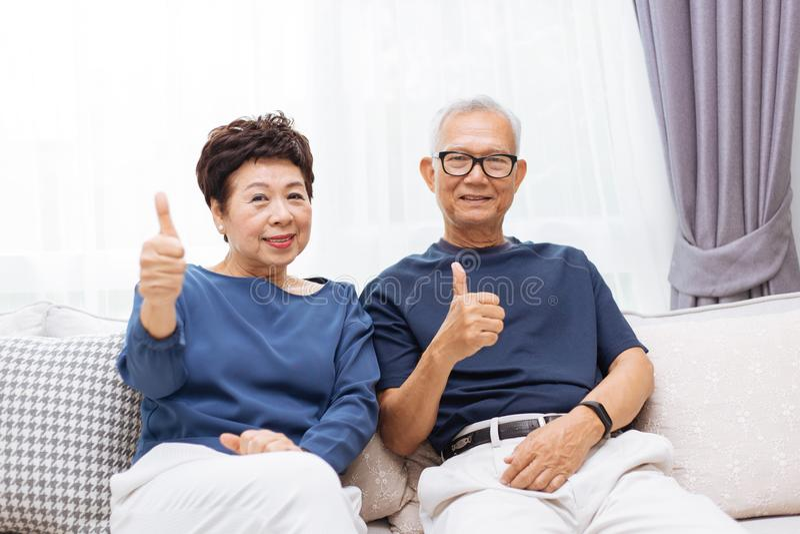 Pares asiáticos superiores que olham a câmera e que dão os polegares acima ao sentar-se no sofá em casa imagens de stock royalty free