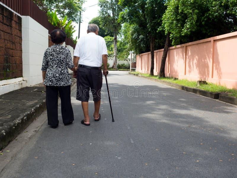 Pares asiáticos superiores românticos felizes que andam e que guardam as mãos na estrada na vila O conceito de pares superiores e foto de stock royalty free