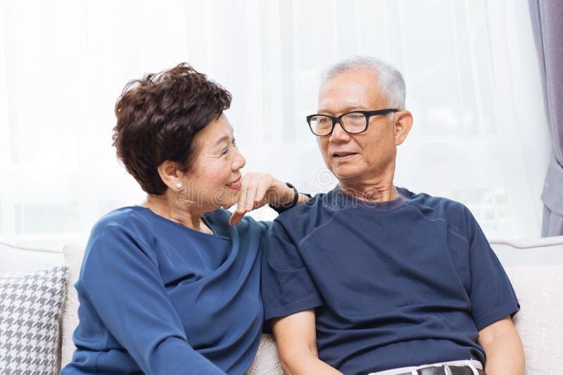 Pares asiáticos superiores românticos que riem e que sentam-se no sofá em casa imagem de stock royalty free