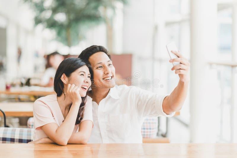 Pares asiáticos usando smartphone al selfie interior foto de archivo