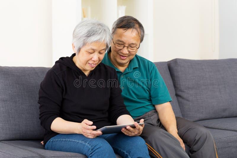Pares asiáticos usando a tabuleta junto imagem de stock royalty free