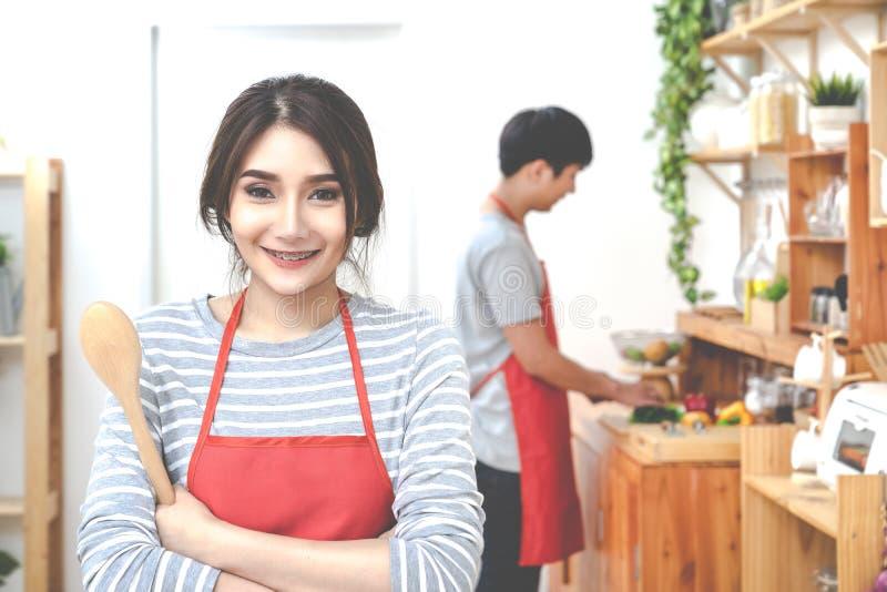 Pares asi?ticos jovenes atractivos que llevan el delantal anaranjado casual que cocina la comida en cocina de madera en casa o el fotos de archivo