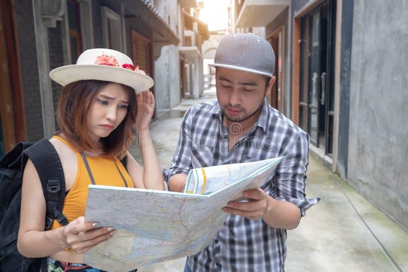 Pares asi?ticos jovenes que sostienen el mapa que mira la direcci?n el vacaciones de la luna de miel foto de archivo libre de regalías
